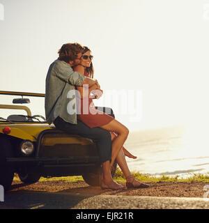 Junges Paar in Liebe umarmen und küssen. Junger Mann und Frau sitzen auf der Motorhaube. Romantische junges Paar auf Roadtrip.