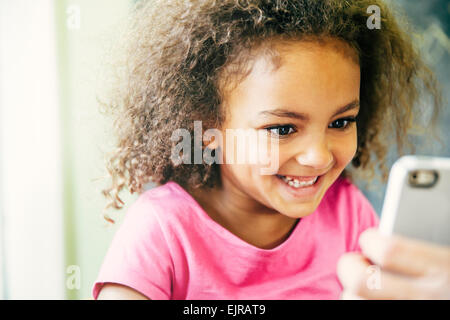 Gemischte Rassen Mädchen mit Handy zu Hause - Stockfoto