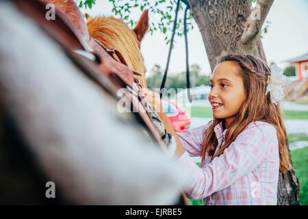 Kaukasische Mädchen Befestigung Sattel am Pferd - Stockfoto
