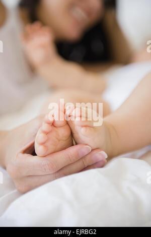 Nahaufnahme von Mischlinge Mutter hält Füße des Babys Stockfoto