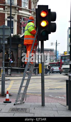 Ampel-Reparatur, ein Arbeiter auf einer Leiter mit Sicherheitsgurt ...