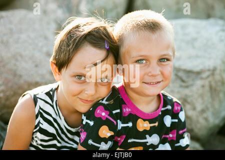 Porträt von Bruder und Schwester lächelnd auf Felsen im Park sitzend - Stockfoto