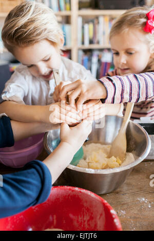 Hinzufügen von Zutaten in Teig beim Backen zu Hause Geschwister - Stockfoto