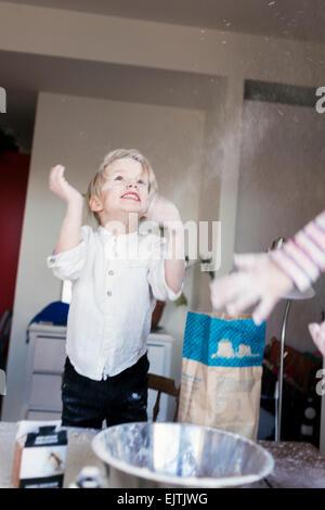Fröhlicher Junge mit Mehl zu Hause spielen - Stockfoto