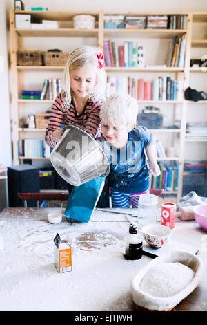 Bruder und Schwester mit Mehl zu Hause spielen - Stockfoto