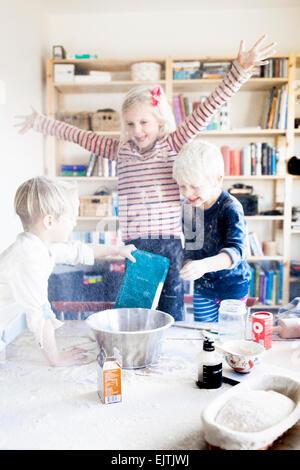 Spielerische Geschwister mit Mehl zu Hause spielen - Stockfoto