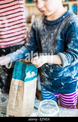 Unordentliche junge Mehl beim Backen zu Hause halten - Stockfoto