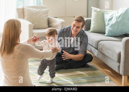Glückliche Eltern helfen Söhnlein (2-3 Jahre) zu Fuß im Wohnzimmer - Stockfoto