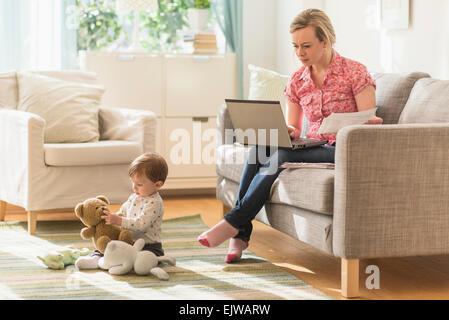 Arbeiten Mutter und Sohn (2-3 Jahre) im Wohnzimmer - Stockfoto