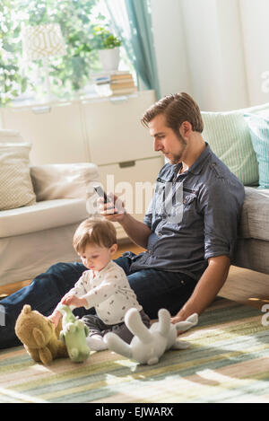 Vater sitzt auf Boden mit kleinen Sohn (2-3 Jahre) in Wohnzimmer und SMS-Nachricht - Stockfoto
