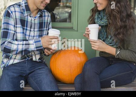 USA, Staat New York, New York City, Brooklyn, junges Paar sitzt auf der Bank mit Kaffeetassen