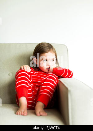 Mädchen (4-5) im Schlafanzug auf sofa - Stockfoto