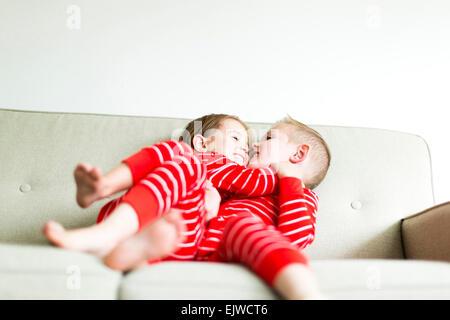 Geschwister (2-3, 4-5) im roten Schlafanzug spielen auf sofa - Stockfoto