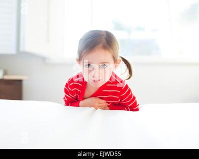 Mädchen (4-5) stützte sich auf Bett - Stockfoto