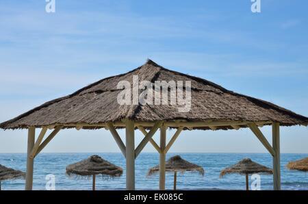 Reihe von Stroh Schatten Sonnenschirme am Strand von Marbella, Spanien. - Stockfoto