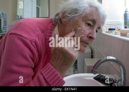 Ältere Frau Auftragen der Creme auf ihr Gesicht in Bad - Stockfoto