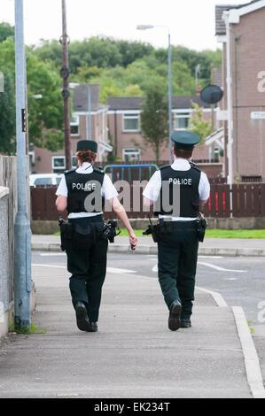 Weibliche und männliche Polizisten zu Fuß auf dem Gehweg einer Straße in einem Wohngebiet. - Stockfoto