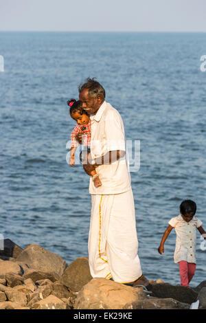 Alten indischen Mann trägt ein junges Mädchen am Strand von Pondicherry oder Puducherry, Tamil Nadu, Südindien - Stockfoto