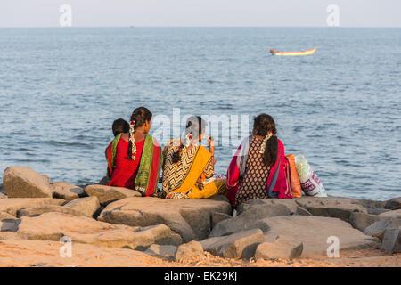 Bunt gekleidete Mädchen sitzen am Ufer bei Pondicherry, oder Puducherry, Tamil Nadu, Südindien mit Blick auf das - Stockfoto