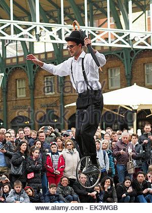 Ein Seiltänzer auf einem Einrad unterhaltsam eine Menschenmenge in Covent Garden London UK - Stockfoto