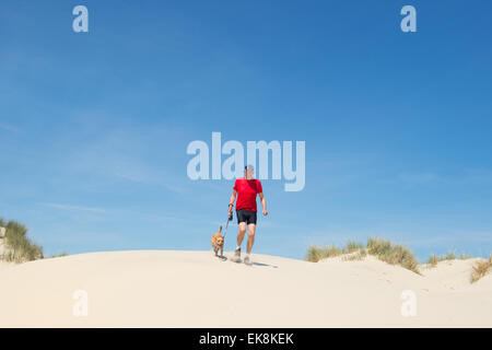 Senior Läufer mit Hund in Natur Dünen - Stockfoto