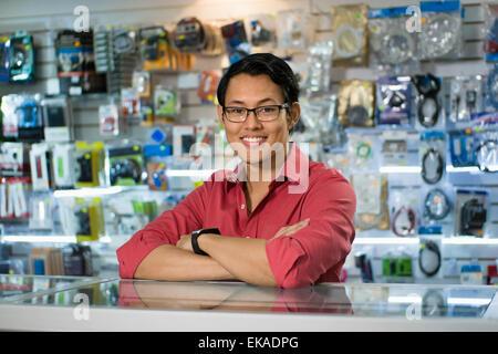 Porträt des jungen chinesischen Mann arbeitet als Angestellter in Computer und Technik Shop, lächelnd in die Kamera - Stockfoto