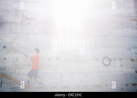Junge Klettern entlang der Wand - Stockfoto