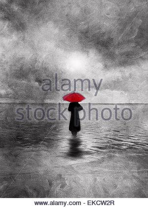 Atmosphärische einsame Frau mit roten Regenschirm waten im Wasser - Stockfoto