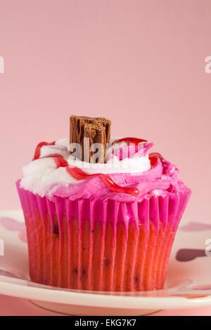 Raspberry Ripple Cupcake mit Schokolade Flocken auf Herz Teller setzen auf rosa Hintergrund - Stockfoto