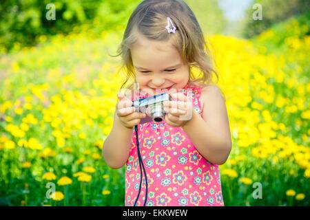 Kleines Mädchen fotografieren auf einer Wiese - Stockfoto