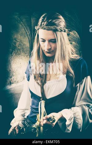 Mittelalterliche Frau, die einen Dolch hält