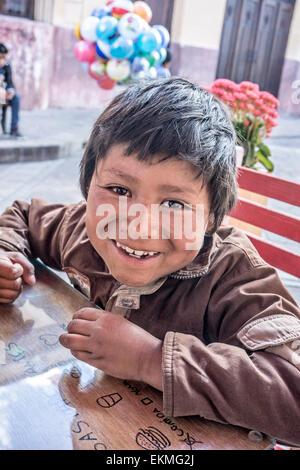 schelmischen kleinen indigenen mexikanischen indischen jungen Kind Straßenhändler nähert sich Tabelle der Touriists - Stockfoto