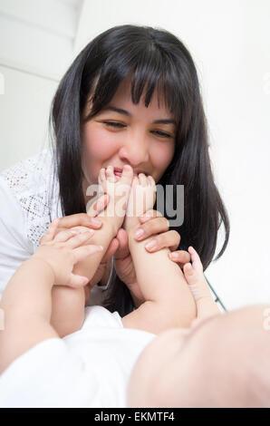 liebevolle junge Mutter Babys Fuß küssen - Stockfoto