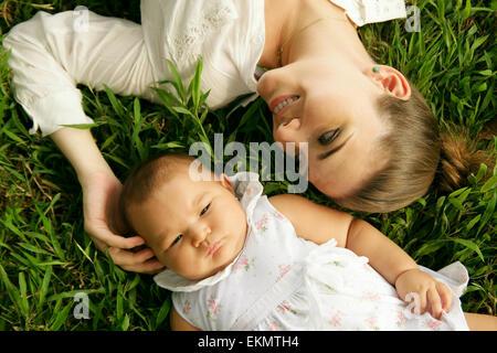 Junge Frau mit ihrer kleinen Tochter, auf dem Rasen im Park entspannen. Die Mutter ihrem Kleinkind Kopf berührt - Stockfoto