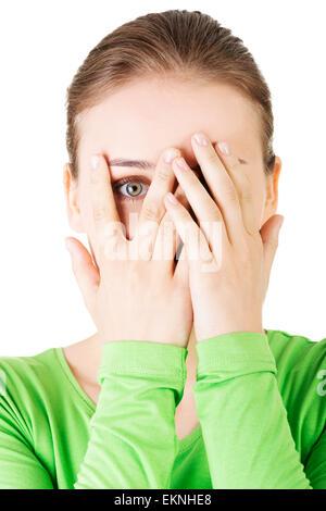 Schüchtern oder ängstlich Teenagerin spähen durch überdachte Fläche - Stockfoto