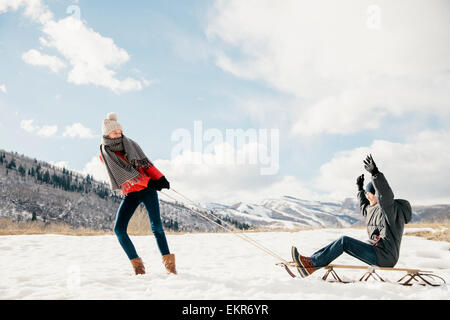 Ein junges Mädchen ihren Bruder auf einem Schlitten durch den Schnee ziehen. - Stockfoto