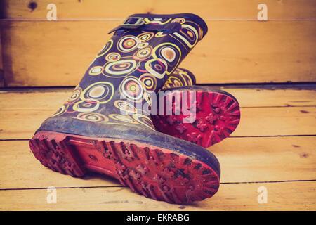 Ein paar Gummistiefel (gumboots) auf einem Holzboden. - Stockfoto