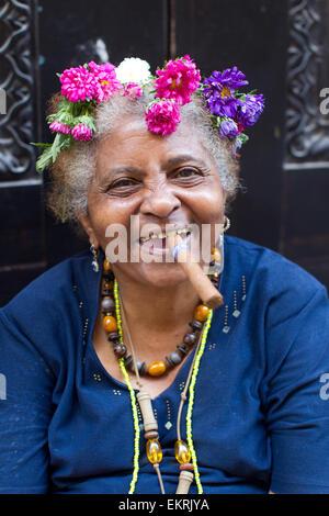 Eine ältere Frau mit Blumen im Haar, raucht eine Zigarre in Havanna, Kuba - Stockfoto