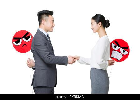 Geschäftsperson Händeschütteln mit wütenden Emoticon steht hinter ihrem Rücken - Stockfoto