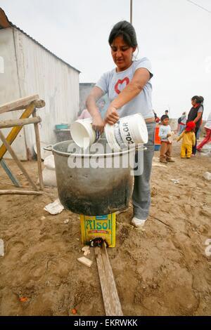 Frau gießt Wasser in Topf, Lima, Peru - Stockfoto