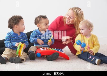 Knoxville, Tennessee, Vereinigte Staaten von Amerika; Eine Frau mit drei kleinen Kindern, die Instrumente spielen - Stockfoto