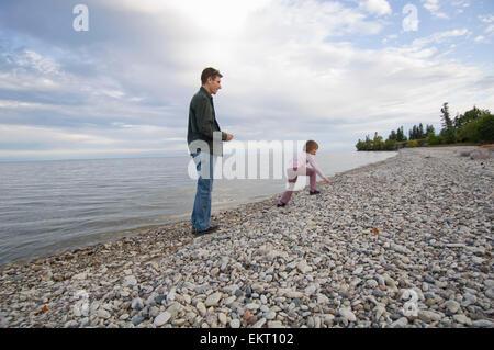 Vater und Tochter am felsigen Ufer des Lake Winnipeg, Hecla Island, Manitoba, Kanada - Stockfoto