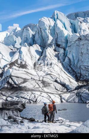 Blick auf das Gesicht des Matanuska Gletscher mit zwei Eiskletterer im Vordergrund, Yunan Alaska, Sommer, USA. - Stockfoto