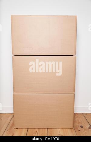 Stapel von Umzugskartons auf Holzboden - Stockfoto