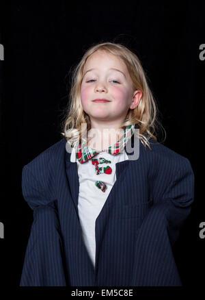 Porträt eines jungen Mädchens putzt sich in Erwachsene Kleidung auf einem schwarzen Hintergrund. - Stockfoto