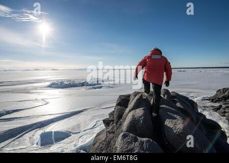 Ein Mann wandert bis zum Ende von einem Felsvorsprung mit Blick auf der Ross-See am Kap Royds, Antarktis. - Stockfoto