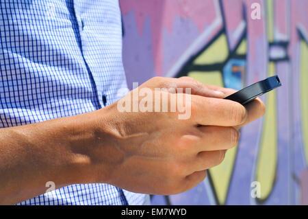 ein junger Mann mit einem Smartphone im Freien in einem städtischen Umfeld - Stockfoto