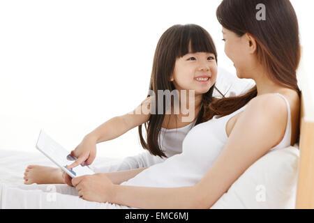 Mutter und Tochter verwenden Tablet-Computer im Bett - Stockfoto