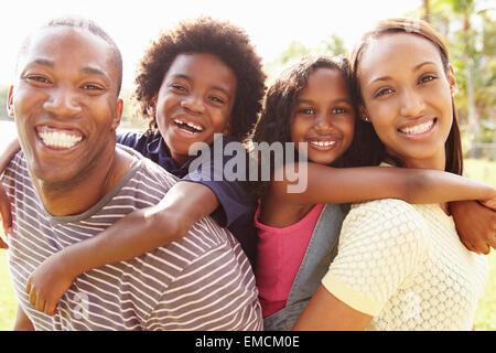 Eltern, Kinder Huckepack-Fahrt im Garten - Stockfoto