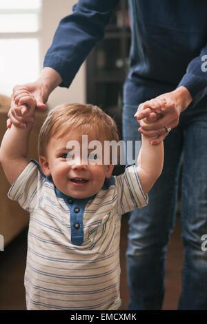 Kleiner Junge mit Hilfe von Mutter laufen lernen - Stockfoto